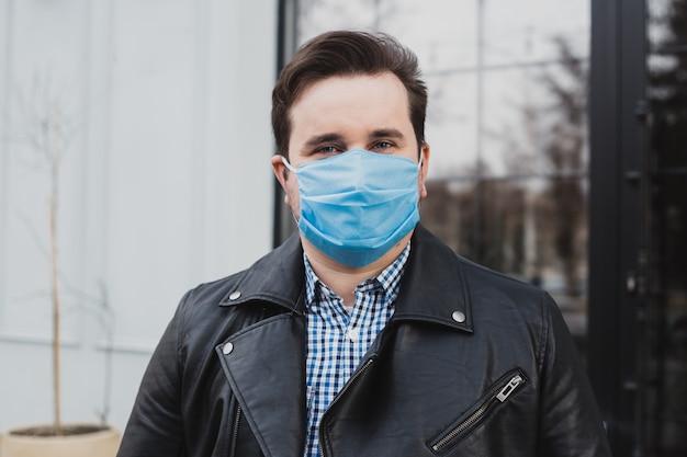 Homme au masque sur un fond de café fermé, coronavirus, maladie, infection, quarantaine, masque médical