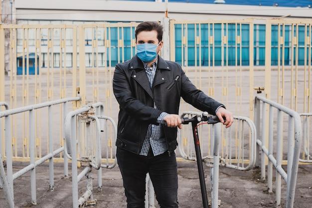 Homme au masque sur fond de clôture avec scooter électrique