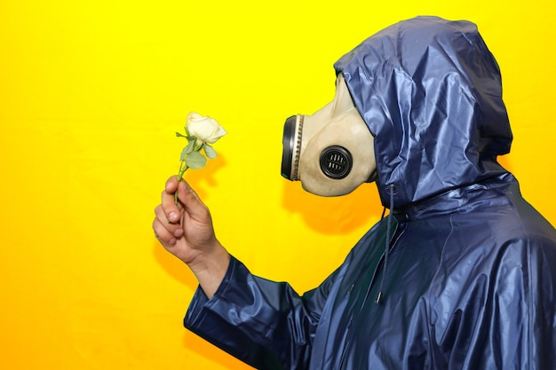 Homme au masque à gaz tenant une fleur isolée sur fond jaune. influence du rayonnement. pollution environnementale. notion de tchernobyl. une énergie nucléaire dangereuse. désastre écologique.
