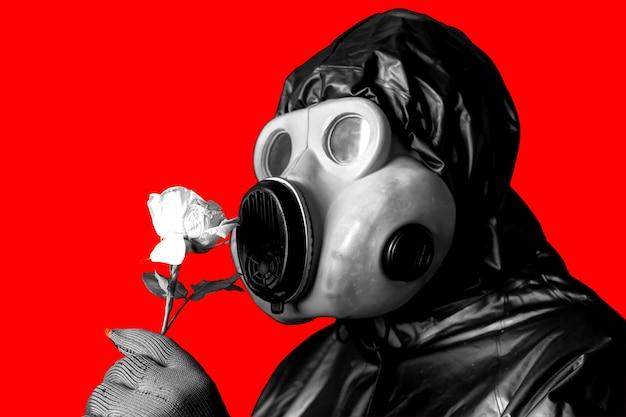 Homme au masque à gaz tenant une fleur isolée sur fond rouge. influence du rayonnement. pollution environnementale. notion de tchernobyl. une énergie nucléaire dangereuse. désastre écologique.