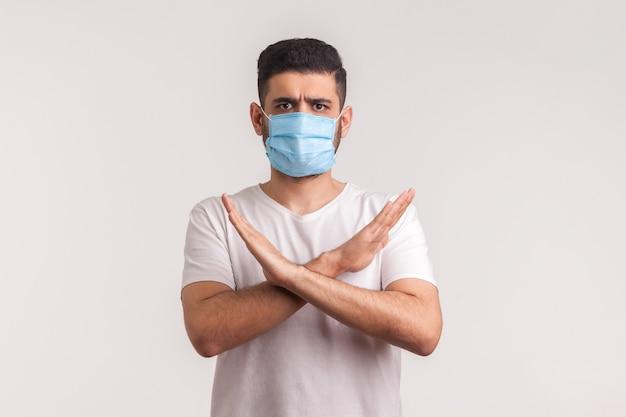 Homme au masque hygiénique debout avec les bras croisés, arrêt des gestes, avertissement de l'épidémie de coronavirus