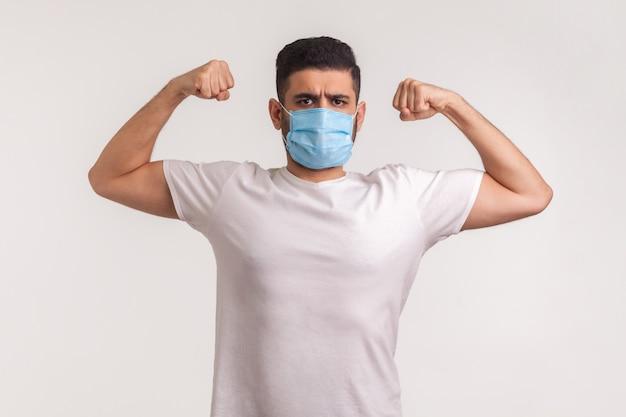 Homme au masque hygiénique montrant la force et l'immunité pour se remettre d'une maladie contagieuse
