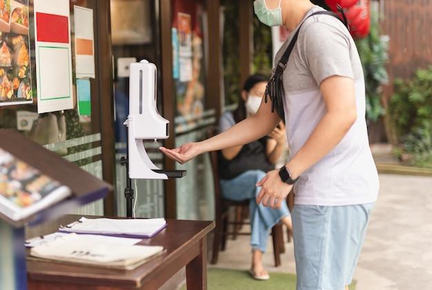 Homme au masque médical à l'aide d'un distributeur automatique de gel d'alcool pulvérisant sur sa main.