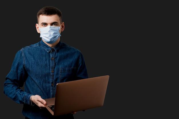 Homme au masque médical avec ordinateur portable