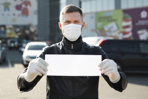 L'homme au masque médical de protection tient une pancarte vide