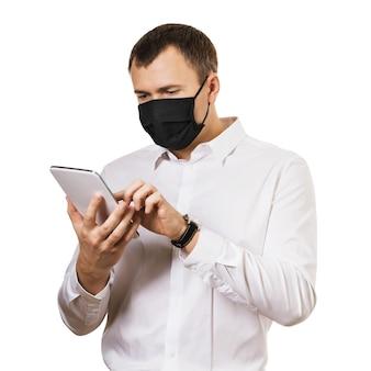 Homme au masque médical avec une tablette numérique dans les mains isolées sur fond blanc