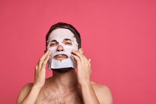 Homme au masque de nettoyage sur fond rose gesticulant avec les mains torse nu vue recadrée. photo de haute qualité