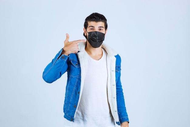 Homme au masque noir pointant sur son masque.