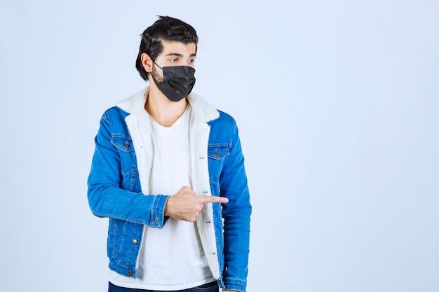 Homme au masque noir pointant vers le côté droit.