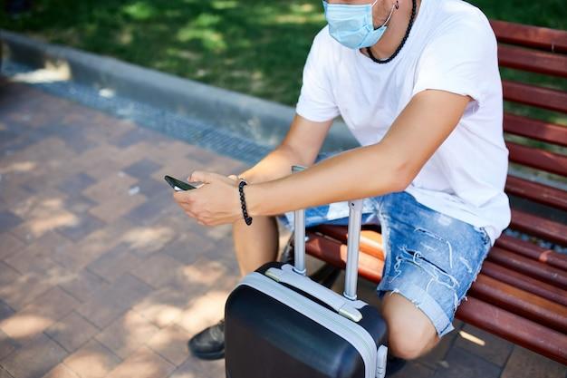 Homme au masque de protection, assis dans le parc en plein air avec une valise et un téléphone portable