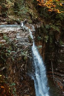 Homme au sommet de la cascade dans l'espace de copie de la forêt d'automne