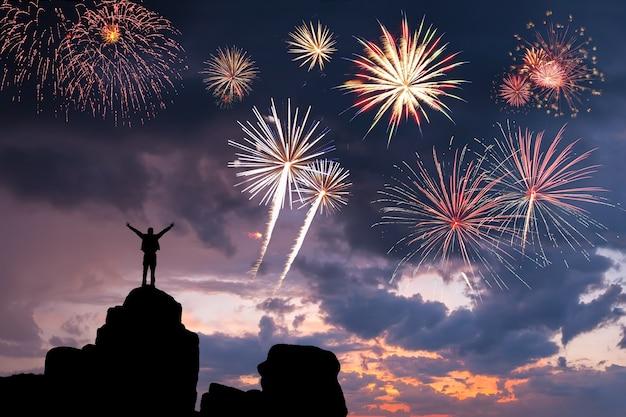 Un homme au sommet d'une montagne heureux du succès, des feux d'artifice dans le ciel