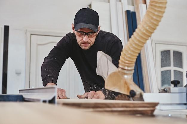 L'homme au travail scie circulaire à bois une machine qui scie des panneaux de particules de bois et des panneaux de fibres