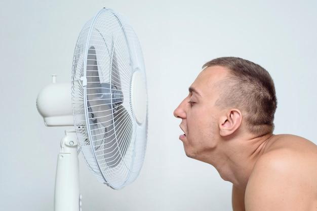 L'homme au visage couvert de chaume souffre de la chaleur et tente de se rafraîchir près du ventilateur.