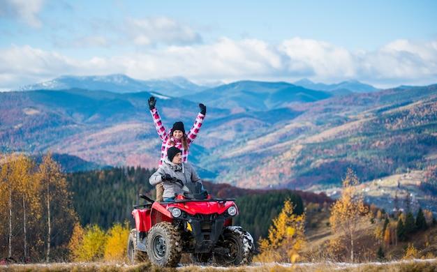 Homme au volant d'un quad, femme assise derrière lui et levant les mains en l'air sur une route de montagne