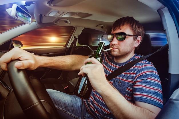 Homme au volant de la voiture et boire de la bière
