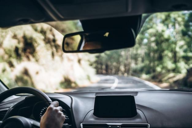 Homme au volant d'une voiture avec vue de l'intérieur.