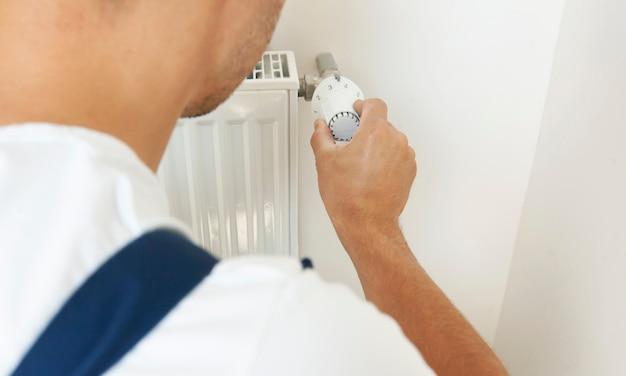 L'homme augmente la température du radiateur en ajustant le thermostat