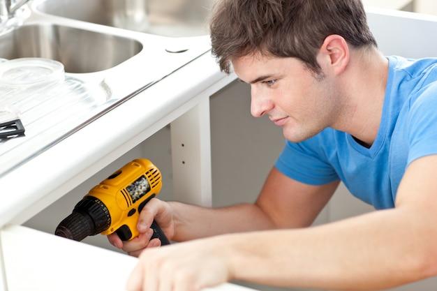 Homme auto-assuré tenant une perceuse en train de réparer un évier de cuisine