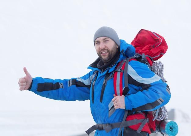 Homme auto-stoppeur sur la route d'hiver. concept de voyage.