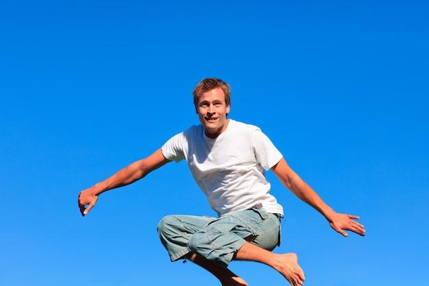 Homme autosuffisant sautant sur un fond bleu