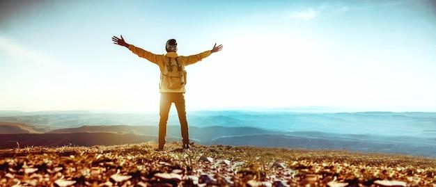 Homme aux bras au sommet de la montagne