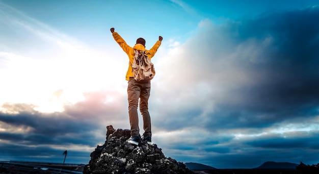 Homme aux bras célébrant au sommet des montagnes