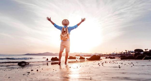 Homme aux bras célébrant le succès sur la plage au coucher du soleil