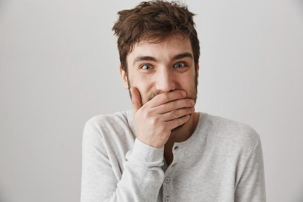 L'homme aux cheveux ballottés glousse, couvre la bouche