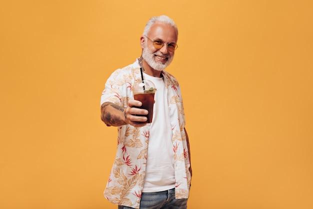 Un homme aux cheveux blancs en chemise de plage tient du thé froid sur un mur orange