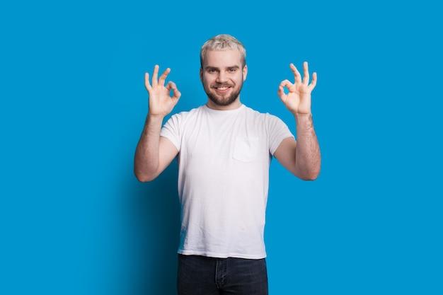 Homme aux cheveux blonds et belle barbe fait signe le signe d'approbation tout en posant dans un t-shirt blanc sur un mur bleu