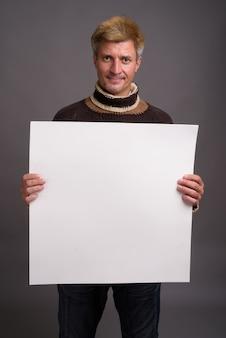 Homme aux cheveux blonds portant un pull à col roulé isolé contre un mur gris