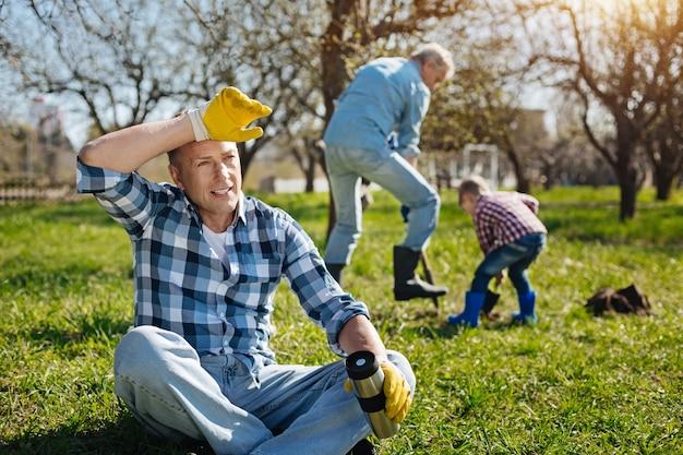 Homme aux cheveux bruns adultes tenant une tasse thermos, assis sur l'herbe et se reposer pendant que son père et son fils ramassent le sol derrière