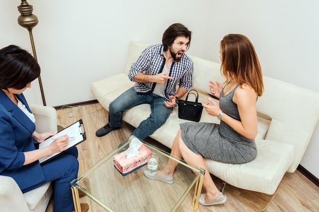 Un homme aux cheveux bruns et barbu crie et hurle à sa femme. l'homme est malheureux et fou. la femme le regarde et lui parle. le docteur fait son travail et ne remarque rien.