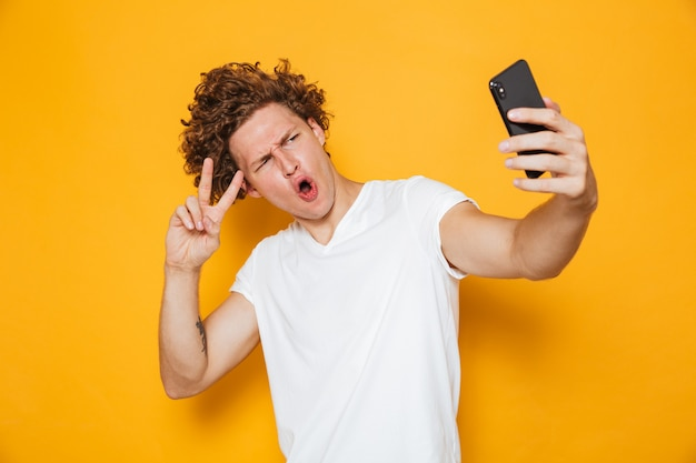 Homme aux cheveux bruns montrant le signe de la paix à la caméra tout en prenant selfie sur smartphone