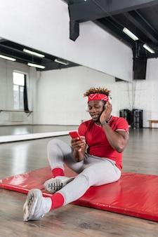 Homme aux cheveux courts actif étant de bonne humeur alors qu'il était assis sur le sol et regardant sur son smartphone entre les entraînements