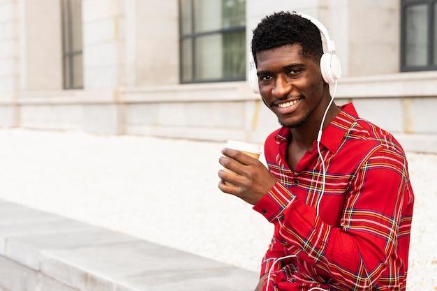 Homme aux cheveux courts, écouter de la musique avec des écouteurs