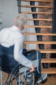 Un homme aux cheveux gris handicapé sur un fauteuil roulant près des escaliers
