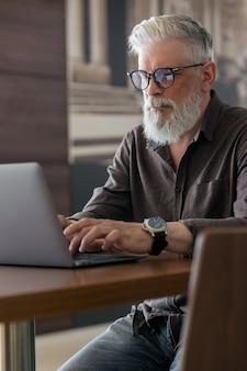 Un homme aux cheveux gris incroyablement beau et élégant de cinquante ans travaillant avec un ordinateur portable