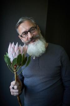 Homme aux cheveux gris avec des lunettes et une barbe tient une protea rose dans ses mains