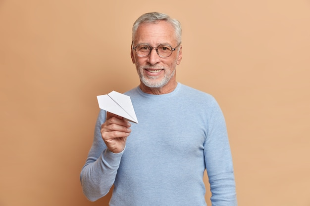Homme aux cheveux gris mature confiant satisfait avec sourire détient avion en papier fait main étant sûr que dans un avenir réussi porte des lunettes et un cavalier bleu isolé sur un mur marron