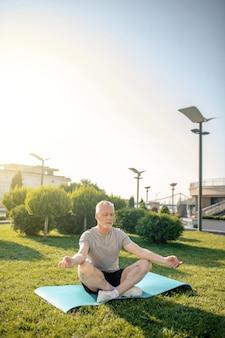 Homme aux cheveux gris méditant en posture de lotus avec les mains dans gyan mudra