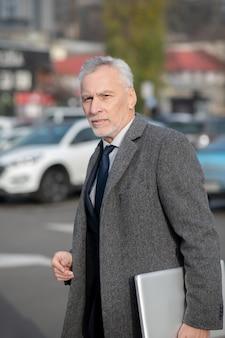 Homme aux cheveux gris portant un manteau gris à la fatigue en traversant la rue