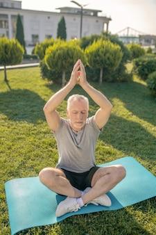 Homme aux cheveux gris pratiquant le yoga à l'extérieur, levant les mains au-dessus de la tête
