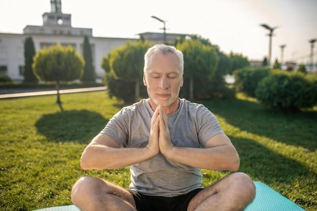 Homme aux cheveux gris pratiquant le yoga à l'extérieur, les mains en namaste