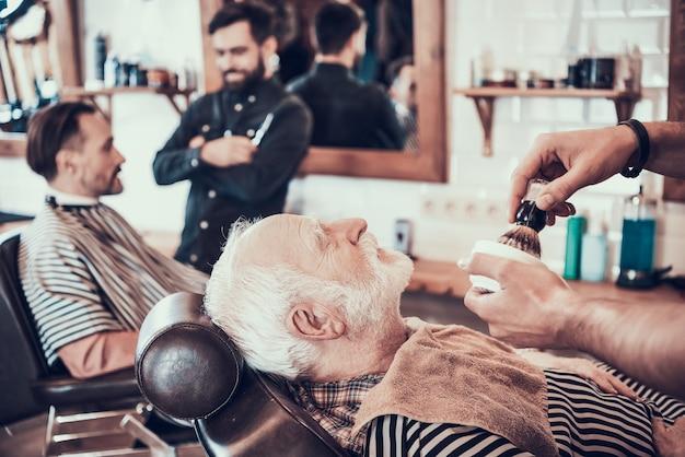 Homme aux cheveux gris se rasant se préparer dans un salon de coiffure