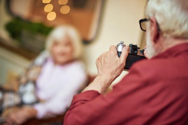 Homme aux cheveux gris tenant un appareil photo et allant prendre une photo de son épouse