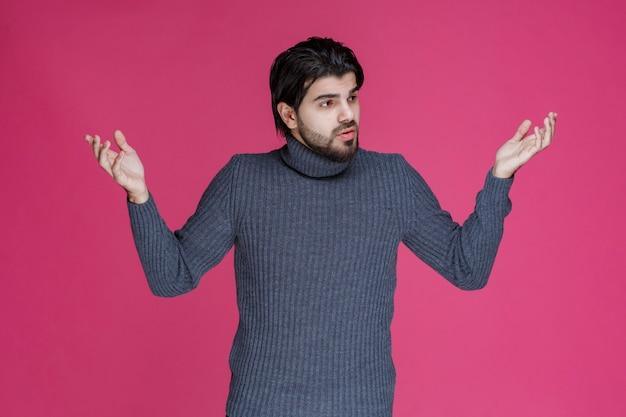 L'homme aux cheveux longs et à la barbe ouvre les mains et a l'air confus ou inexpérimenté.
