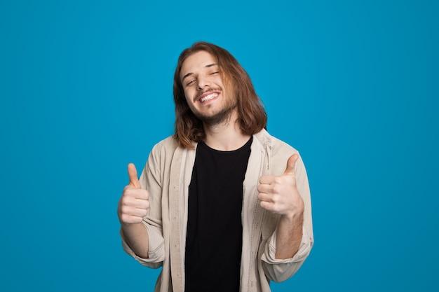 Homme aux cheveux longs gesticulant le signe comme la publicité quelque chose sur le mur bleu