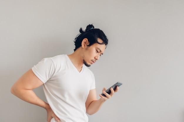Homme aux cheveux longs en t-shirt décontracté blanc utilise un smartphone